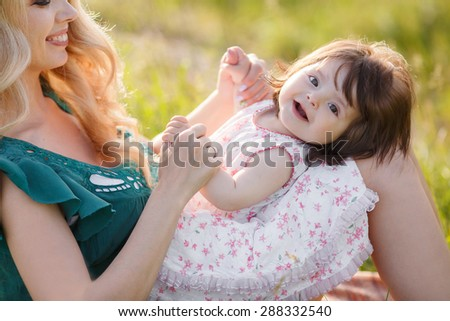 Mother playing with baby girl outdoor in summer park. Happy mother and her little daughter at spring day. Happy joyful family portrait.  - stock photo