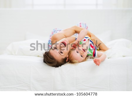 Mother playing with baby in bed - stock photo