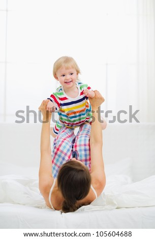 Mother playing with baby in bedroom - stock photo
