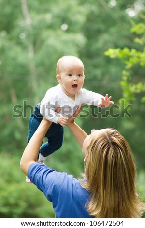 Mother playing with baby in the park - stock photo