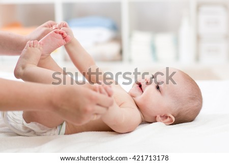 Mother playing with baby. Mom massaging little child.