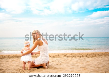 Mother playing with baby on beach. Rear view. - stock photo