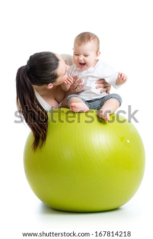 mother playing with baby on fit ball - stock photo