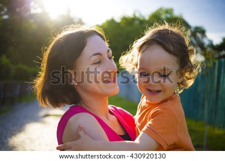 Mother playing with baby on the street and they have fun together. - stock photo