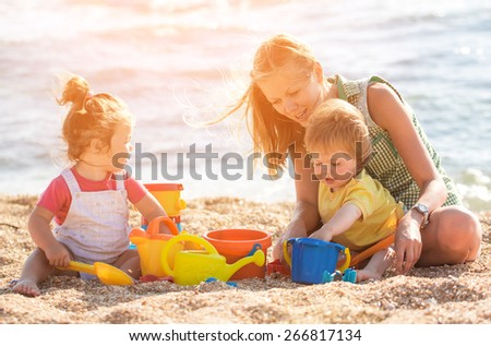Mother playing with children on the beach
