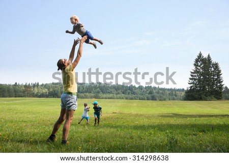 Mother playing with children, throwing a toddler in air, laughing and playing, and her older son and daughter jumping and running on a meadow. Active lifestyle, family time, modern parenting concept.  - stock photo