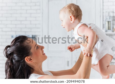 Mother playing with daughter, holding her up. - stock photo