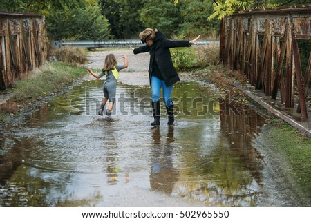 mother playing with daughter in the pool of water