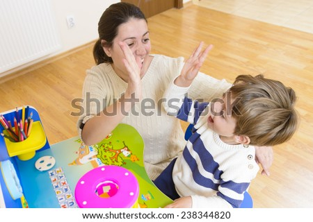Mother playing with her child some creativity game and encouraging him - stock photo
