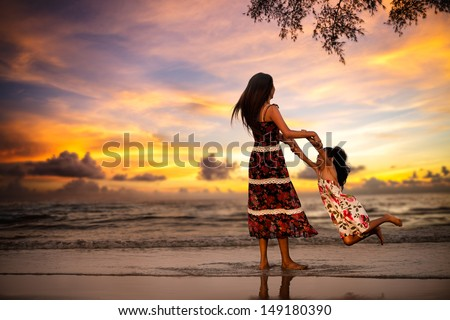 Mother playing with her daugher on the beach in evening - stock photo