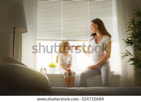 mother playing with her daughter - stock photo
