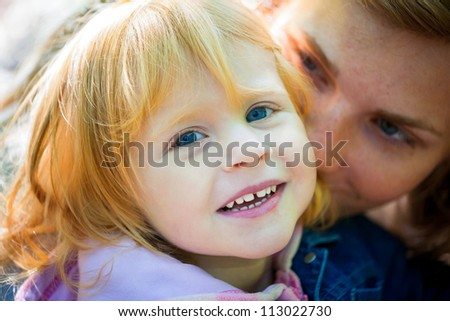 Mother playing with her daughter - outdoor shot - stock photo