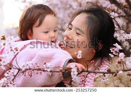 Mother Playing with her Infant Daughter amongst the Flowers in narrow focus - stock photo