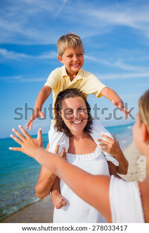 Mother playing with her kids at the beach