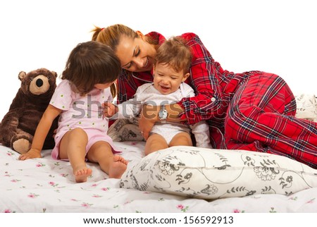 Mother playing with her kids in the bed and having fun together