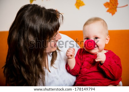 Mother playing with her smiling baby - child has red clown nose - stock photo