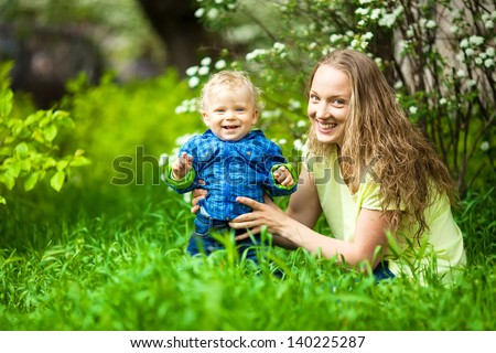 Mother playing with her toddler child. Outdoors portrait.