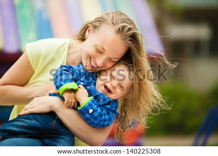 Mother playing with her toddler child. Outdoors portrait.  - stock photo