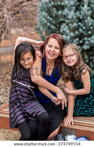 Mother playing with her young daughters outside at a park in Reno, Nevada, USA.