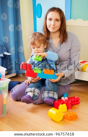 Mother playing with kid with plastic construction blocks