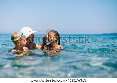 Mother Playing with Two Kids in Sea Water Swimming Bathing Laughing Enjoying