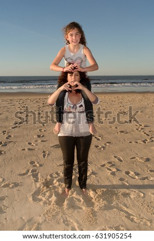 mother plays with her daughter on her shoulders on the sand of the beach