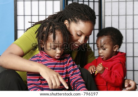 Mother plays with her two sons - stock photo