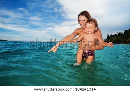 Mother pointing at something interesting in the water - stock photo