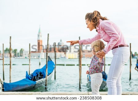 Mother pointing baby on something on grand canal embankment in venice, italy - stock photo