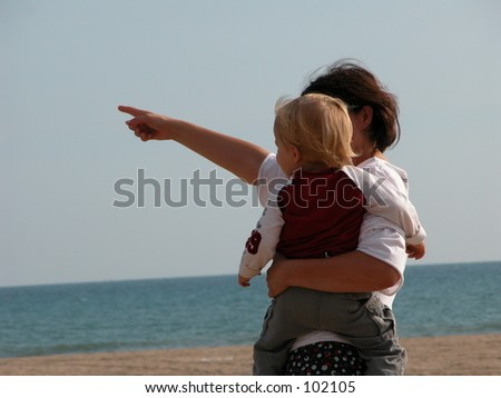 Mother pointing out something to her child on the beach - stock photo