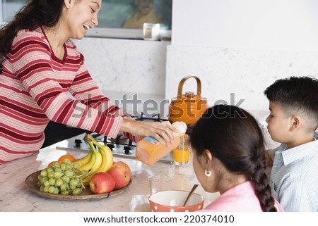 Mother pouring juice for son and daughter - stock photo
