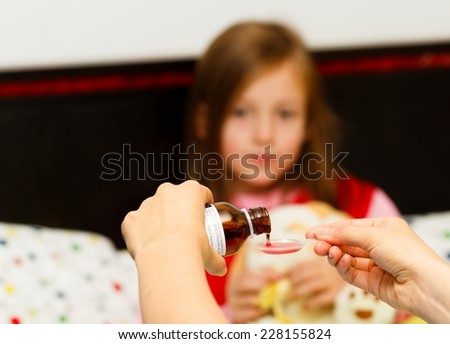 Mother pouring tasty syrup to ease her little girl's cough. - stock photo