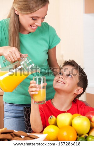 Mother pours orrange juice to her son's glass - stock photo