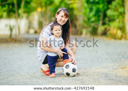 Mother practices her child to play a soccer football, which sport is very good to make a family members have an activity together. - stock photo