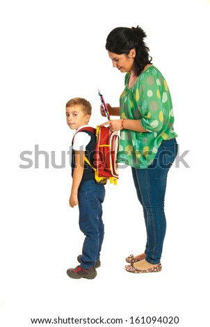 Mother prepare boy for school and giving notebooks isolated on white background - stock photo