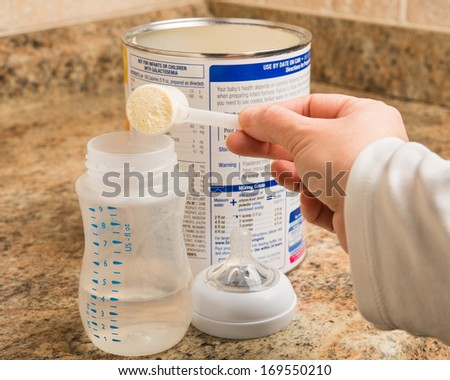 Mother prepares baby milk formula in kitchen - stock photo