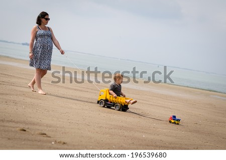 mother pulls her son on the beach - stock photo