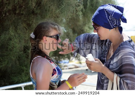 Mother puts sunscreen on her daughter's face at the summer resort - stock photo
