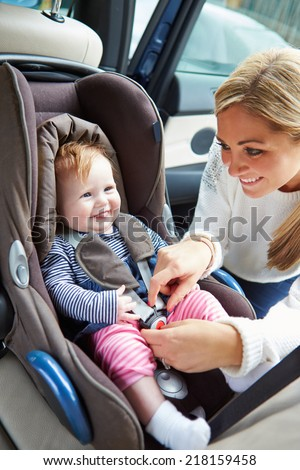 Mother Putting Baby Into Car Seat - stock photo
