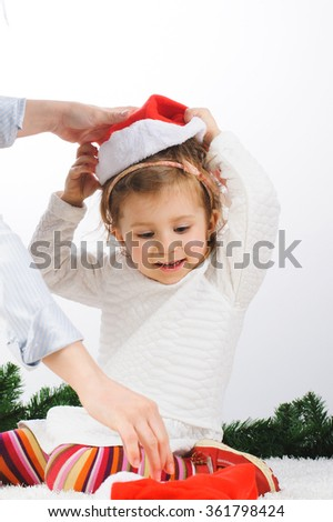 mother putting red santa hat on daughter - stock photo