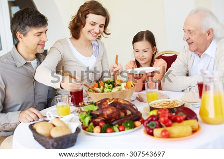 Mother putting salad on plate of daughter