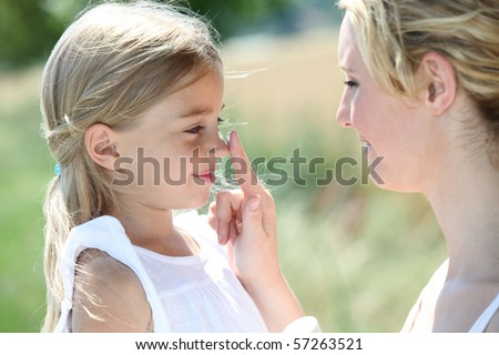 Mother putting sunscreen on her daughter's nose - stock photo