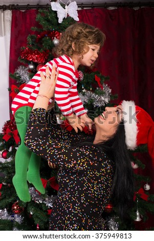 Mother raising her toddler son in front of Christmas tree