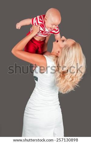 Mother raising up of joyful baby boy in costume isolated on a dark background - stock photo