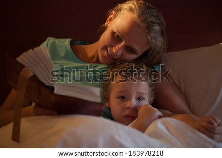 Mother reading a bedtime story to her little son cuddling down alongside him on the bed as he peers over the counterpane at the camera - stock photo