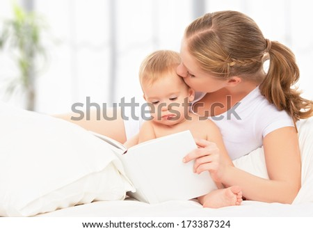 Mother reading a book the baby in bed before going to sleep