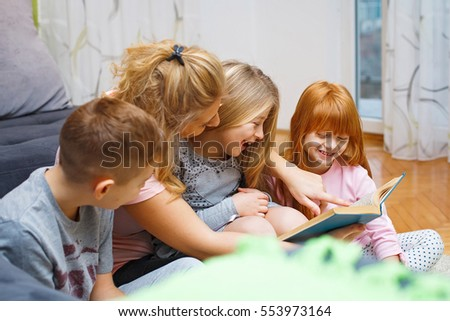 Mother reading a book to her children .