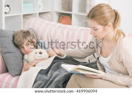 Mother reading a book to her feverish son who is lying on a sofa covered with a grey blanket