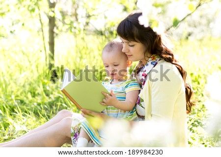 mother reading a book to kid outdoors - stock photo