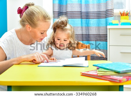 Mother reading a book to little baby. Indoors. - stock photo